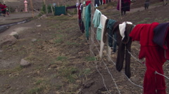 Ecuadorean woman hanging laundry on barbed wire fence Stock Footage