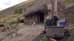 Rural Ecuadorean family in yard of thatched dwelling Stock Footage