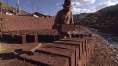 Man stacking adobe blocks at a brickyard in Cusco, Peru Stock Footage