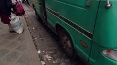 Green bus and passersby on a street in Cusco, Peru Stock Footage