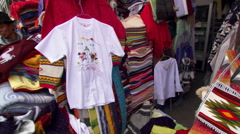 Customers examining garments at an open-air clothes market in Cuenca, Ecuador Stock Footage