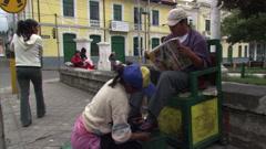 Shoeshine girl shining customer's shoes on  street corner in Cayambe, Ecuador Stock Footage