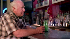 Waist-up portrait of a balding older man sitting at a bar and drinking a beer - stock footage