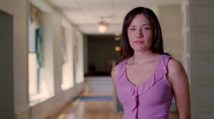 Full-face portrait of a dark-haired young woman standing in a long corridor Stock Footage