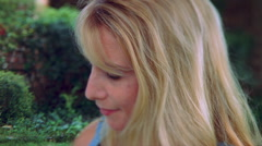 Close-up profile of blonde-haired young woman smiling Stock Footage