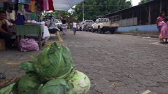 Woman and girl with head baskets walking through Salvadoran marketplace - stock footage