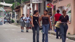Schoolgirls walking toward camera on a Salvadoran street; horseman riding past Stock Footage