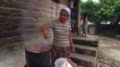 Salvadoran woman stirring bean soup in kettle over outdoor fire Stock Footage