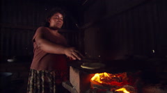 Woman cooking tortillas over fire in dim interior of Salvadoran home Stock Footage