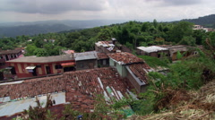 Left pan over roofs of buildings clustered on a wooded slope in El Salvador Stock Footage