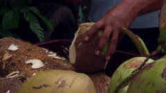Close-up of Salvadoran worker draining liquid from a fresh coconut - stock footage