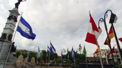 Flags waving near winged statue in La Plaza Libertad, San Salvador Stock Footage