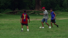 Young Salvadoran men playing soccer in a green field Stock Footage