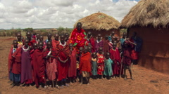 Masai villagers posing for group portrait near thatched huts on East African - stock footage