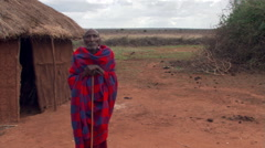 Masai chief leaning on staff outside hut on Tanzanian plain - stock footage