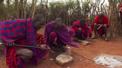 Four young Masai men sharpening knives and smoothing spear shafts - stock footage