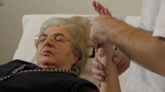 Physiotherapist showing and doing exercises with old female patient, close up. - stock footage