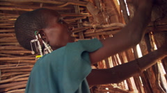 Close-up profile of Masai woman plastering a wall of a hut - stock footage