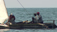 Towri fishermen in a boat with sail and outriggers near Bagamayo, Tanzania Stock Footage