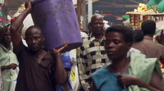 Close view of pedestrians passing camera on a crowded street in Kampala, Uganda Stock Footage