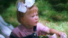Close-up of a little girl picking a petal from a daisy - stock footage