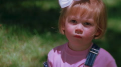 Close-up of a pouting little girl with a white hair bow - stock footage