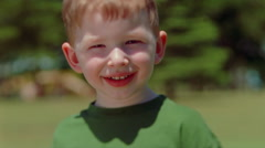 Close-up full-face portrait of a smiling little red-haired boy Stock Footage