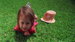 Close-up of little girl lying tummy-down on grass Stock Footage