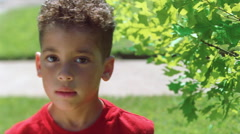 Close-up face of curly-haired little boy in an outdoor setting Stock Footage