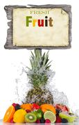 Fresh fruit in water splash and wooden board - stock photo