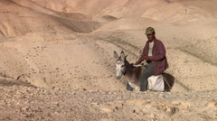 Jordanian man riding donkey with barren desert hills in background Stock Footage