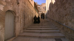 Monks descending stairs at Church of the Holy Sepulcher, Jerusalem Stock Footage