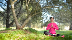caucasian woman practicing meditation in the park - stock footage