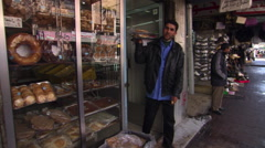 Young man leaving an Israeli bakery with two trays of bread Stock Footage