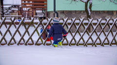 Two cute little boys each on one side of the fence - stock footage