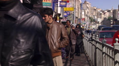 Pedestrians approaching camera on a sidewalk in Amman, Jordan Stock Footage