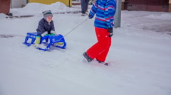 One boy is pulling a little boy on a sled Stock Footage