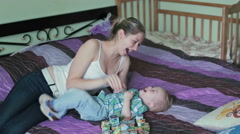 Mother and son having tickle fight in bed Stock Footage