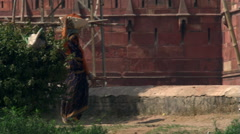 Right pan from scaffolding to men and women working on repairs at Agra Fort Stock Footage