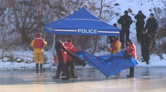 Police officers recover body of missing woman found in pond ice - stock footage