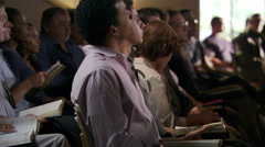 Seated congregation holding Bibles and listening to out-of-frame speaker - stock footage
