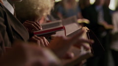 Standing congregation turning to Bible verse, close-up of Bible nearest camera - stock footage