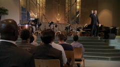 Pastor speaking from top of wide steps to seated congregation - stock footage