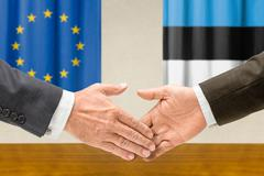 Representatives of the EU and Estonia shake hands - stock photo