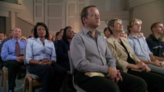 Seated congregation clapping - stock footage