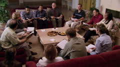 Adult Bible study group seated around low table Stock Footage