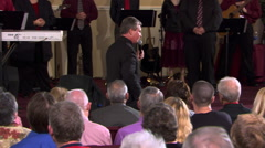 Preacher speaking to seated congregation, musicians on rostrum behind him Stock Footage