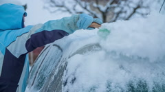 A lady is brushing snow off the roof of a car Stock Footage