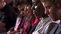 Faces of seated communicants partaking of the bread during Communion Stock Footage