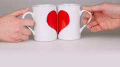 Coffee cups with halves of the heart in hands unite to the one heart. Stock Footage